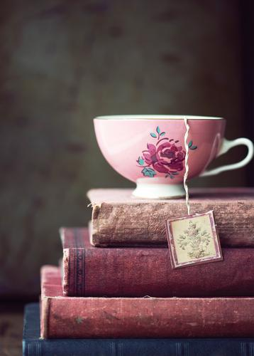 vintage teacup on stack of old books - picture 1