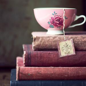 Postcard vintage teacup on stack of old books
