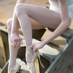 Postcard ballerina tying her pointe shoes
